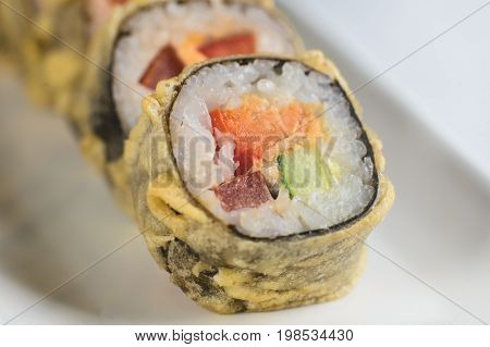 Rolls With Cheese And Fried Salmon On A White Rectangular Plate On A White Background.