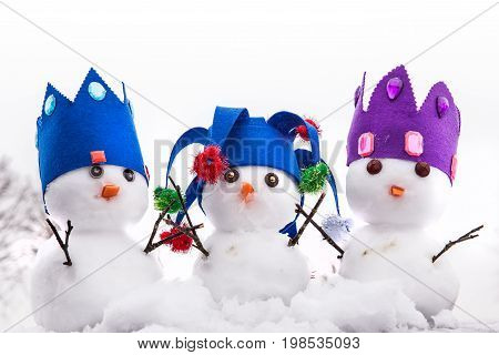 Three cute king snowmen dressed with crowns looking very regal. Snow fall background in a rural winter scene