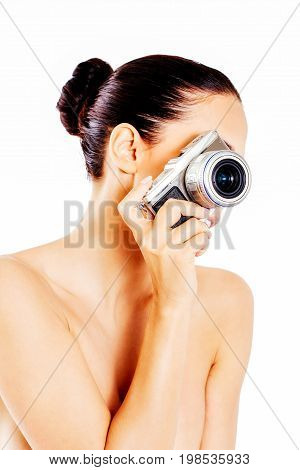 Nude beautiful woman with photo camera. Isolated on white.