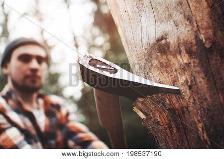 Modern Logger In A Plaid Shirt With An Ax Chopping Wood