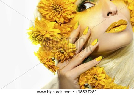 Summer yellow makeup and manicure oval nails on a woman with flowers on a white background.
