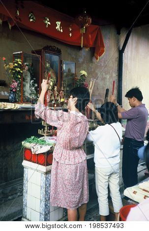 SINGAPORE / CIRCA 1990: Worshipers light candles, burn incense, and pray before sacred sculptures in the Kwan Im Thong Hood Cho Temple.