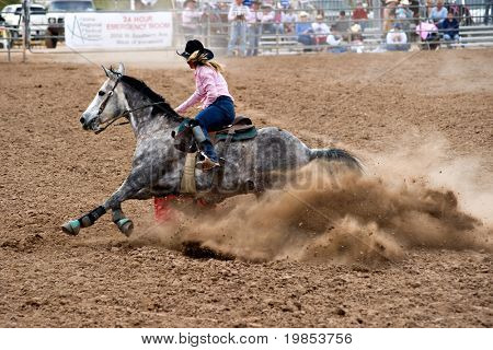 APACHE JUNCTION, AZ - FEBRUARY 26: A female competitor rides a horse in the barrel race competition at the Lost Dutchman Days Rodeo on February 26, 2010 in Apache Junction, Arizona.