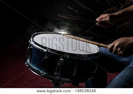 The man is playing snare drum in low light background.