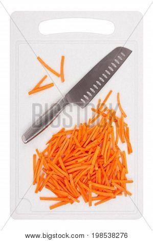 Kitchen knife and sliced carrots on a plastic cutting board closeup top view