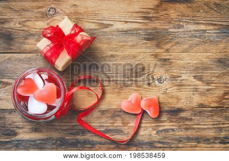 Jelly candy shape heart in glass jar with red ribbon gift box for Valentine's Day on wooden table