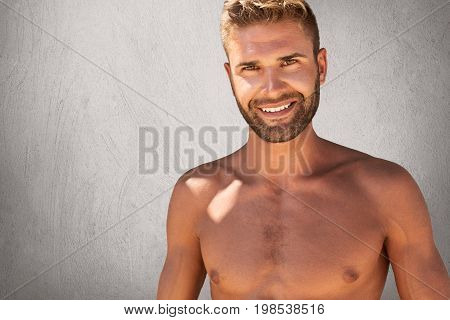 Glad Topless Male With Trendy Hairstyle And Bristle Having Strong Body Builduing Posing Against Grey