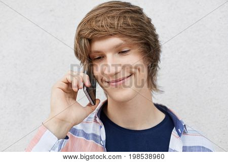 Close Up Portrait Of Handsome Teenage Boy With Trendy Hairstyle, Smiling Gently Having Dimples On Ch
