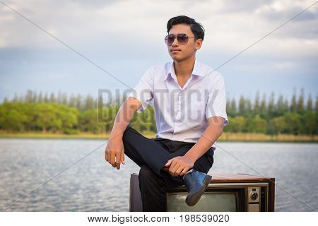 Man Wearing Glasses Sitting On A Pier With Old Televisions.