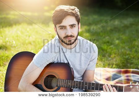 Young Bearded Male Guitarist In Casual T-shirt Sitting With Musical Instrument On Green Grass, Playi