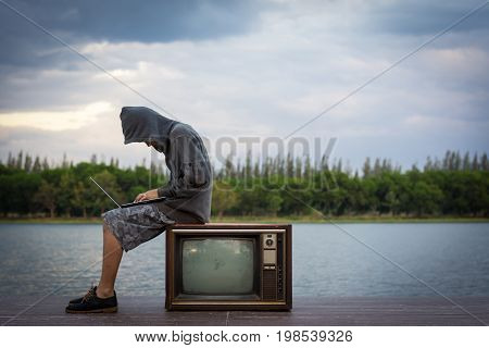 A Young Man Wearing A Hooded Sweatshirt Sitting Near The Old Television.a Hacker With A Laptop.