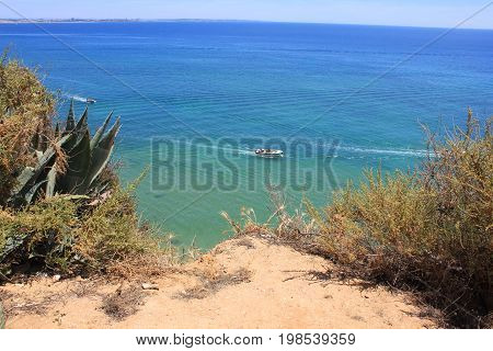Small tour boat in ocean, cliff edge view. Tourist yacht with people on board slowly touring empty sea shore area. Seascape summer sunny day scene with blue sky and turquoise color water from top