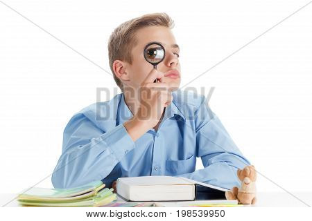 Funny Child schalit with a magnifying glass reading a book at School. Boy studing at table.