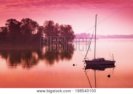 Little sailing boat reflects in the serene water during sunrise. Masuria Poland.