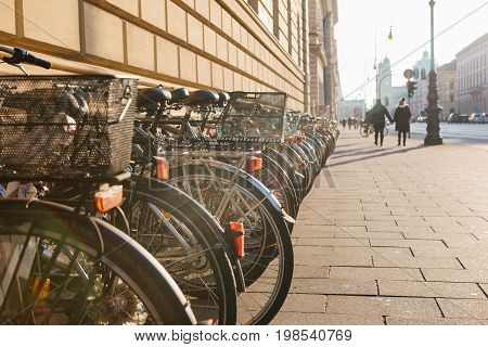 Many bikes in a row on the street in Munich, Bavaria, Germany, Europe. Bicycle parking. Environmentally friendly and healthy means of transportation around the city. healthy lifestyle