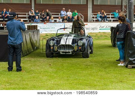 PAAREN IM GLIEN GERMANY - MAY 23 2015: Sports car AC Cobra (replica) discusses moderator Johannes Huebner. The oldtimer show in MAFZ.