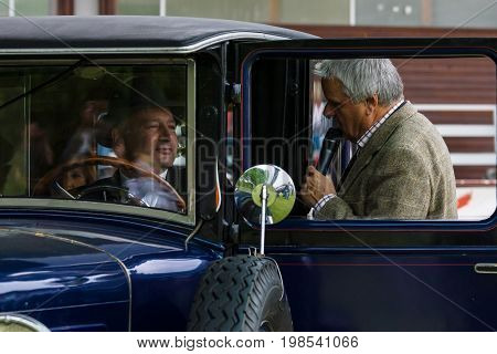 PAAREN IM GLIEN GERMANY - MAY 23 2015: Moderator event Johannes Huebner interviewing the owner of retro car. The oldtimer show in MAFZ.