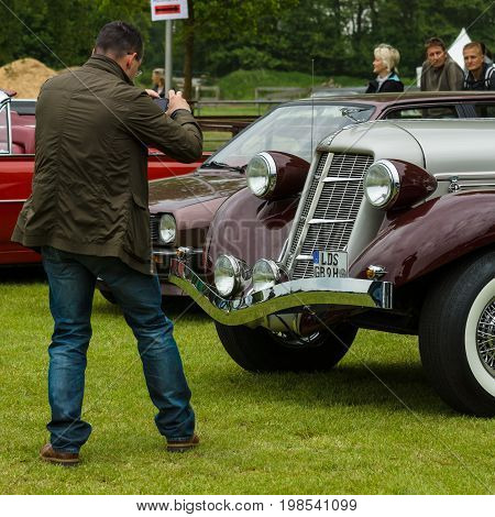 PAAREN IM GLIEN GERMANY - MAY 23 2015: A visitor photographs the vintage car. The oldtimer show in MAFZ.
