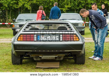 PAAREN IM GLIEN GERMANY - MAY 23 2015: Guest is looking at sports car DeLorean DMC-12. The oldtimer show in MAFZ.