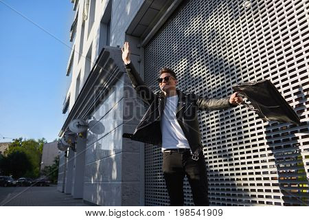 Outdoor lifestyle picture of handsome guy in shades standing on street holding bag in one hand and raising the other waiving it actively hailing a cab while being late to airport or urgent meeting