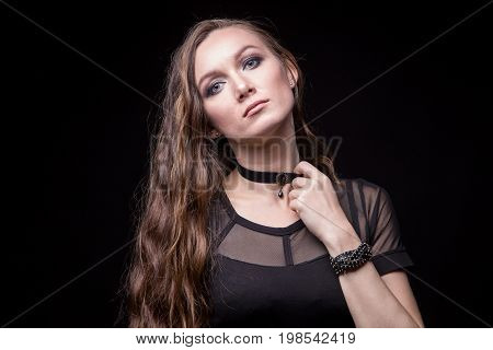 Young blond woman with long hair and choker on black background