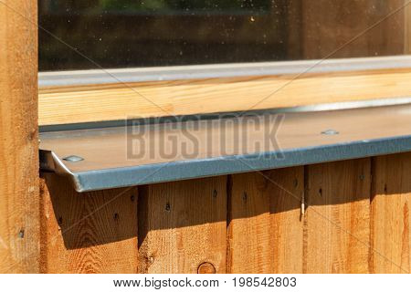 Sheltered window sill. Galvanized sheet metal on the window. Building an eco-house