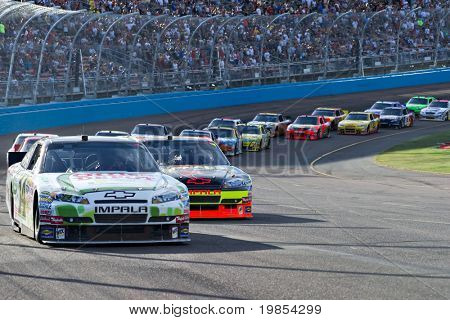 AVONDALE, AZ - APRIL 10: Tony Stewart (#14) leads a group of cars out of turn one at the Subway Fresh Fit 600 NASCAR Sprint Cup race on April 10, 2010 in Avondale, AZ.
