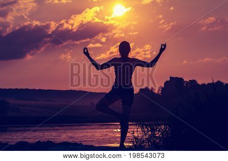 Young woman does yoga or fitness at sunset. Silhouette on the background sun. Summer rest and recuperation. A healthy way of life.