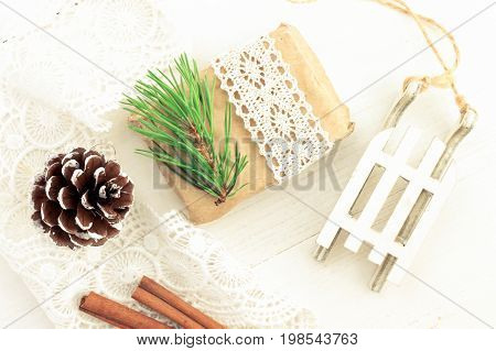 Festive wonderful season theme. Winter time eco decorative items top view. Craft paper gift with lace ribbon and pine bough, little sledges, pine cone.