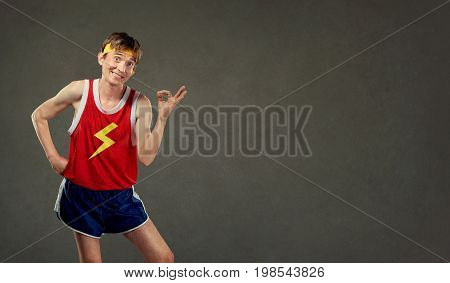 Funny thin man in sports clothes shows his hand okay. Humor in sports.