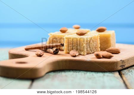 Indian traditional dessert halva wih cinnamon and almonds served on wooden board on blue background copyspace closeup