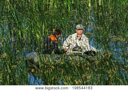 Two poachers on a rubber boat catch fish in the net. Zhitomir Ukraine June 16 2017.