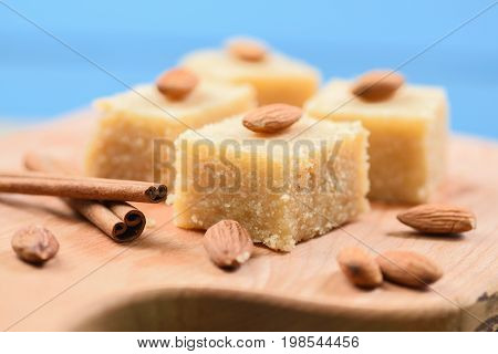 Indian traditional dessert halva made with semolina and milk wih cinnamon and almonds on blue background close up closeup