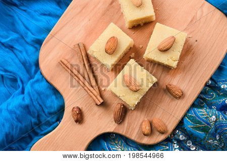 Homemade Indian sweets halva wih cinnamon and almonds served on embroidered blue cloth top view overhead view
