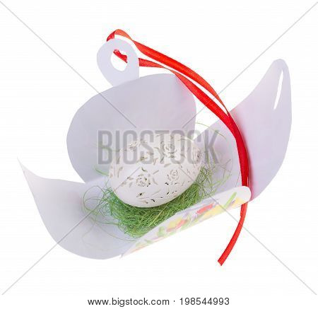 Easter hen's egg with carving in opened gift box. Macro. Isolated on a white background.