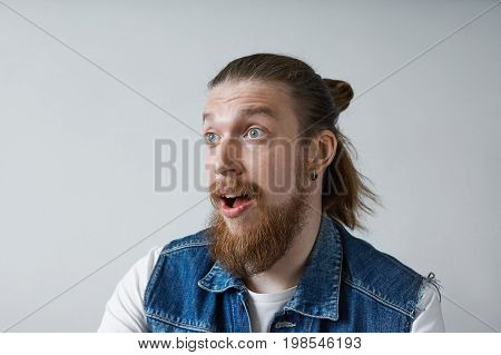 Portrait of excited European guy exclaiming in shock and excitement astonished with some positive news posing in studio keeping mouth wide opened. Human face expressions and emotions body language