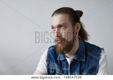 Headshot of fed-up young European hipster man with facial hair and bun rolling his eyes while feeling annoyed or irritated with something having displeased and bored look. Human emotions and feelings