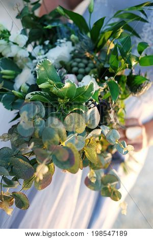 Woman's hand with a big ring holding a beautiful bouquet in sunset light standing outdoors in summer dressed for the event