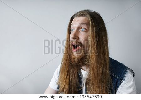 Funny emotional Caucasian male with long messy hair and beard having amazed and shocked expression on his face surprised with shocking unexpected news isolated against grey studio wall background