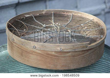 Peneira com grãos de areia por cima da rede