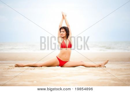 Beautiful woman doing stretches exercise on the beach