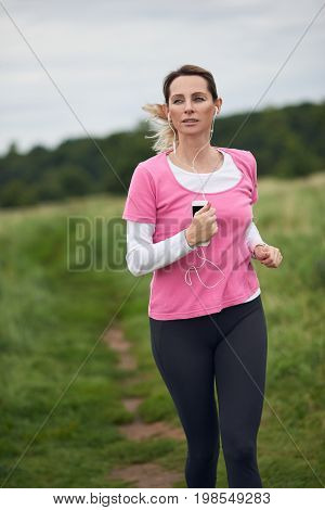 Concentrated woman listening to music running through field copy space to the left