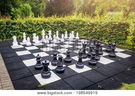 Large outdoor chess game on a garden terrace in a yard with a green hedge and sunshine