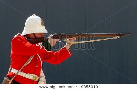 Soldier and rifle at military display.
