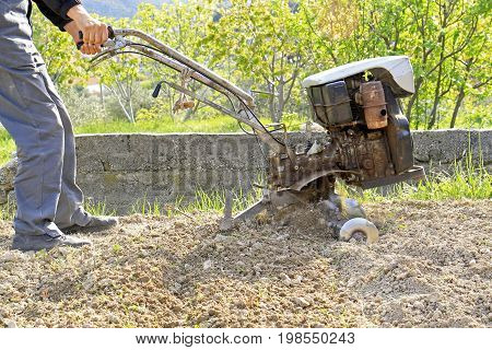 Farmer plowing the earth with the motocultivator