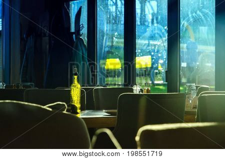 The interior of the restaurant is without visitors. On the table is an empty green bottle, lit by the sun.