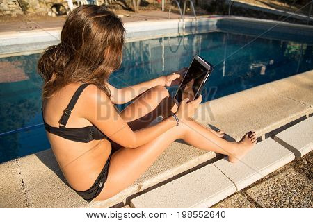 Side view of unrecognizable woman sitting and relaxing with digital tablet on poolside.