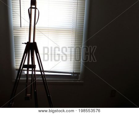 artist's easel silhouetted against sunny window blinds creativity and art concept