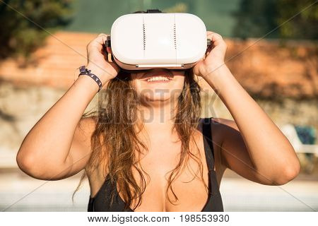 Smiling woman in swimwear using virtual reality glasses sitting on poolside.