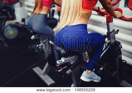 Close-up view of the back of a sporty girl sitting on the seat of a bike simulator in the gym. Concept tightened buttocks, priest.